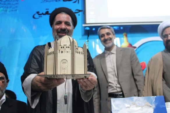 In the polytheistic country of Iran, the regime has founded and funded numerous organizations who as the shrine-obsessed Shias they are, calling for the shrines of al-Baqi' to be rebuild. Here a Rafidi priest holding his future money-making machine (shrine model) in his hands.